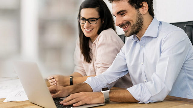 Man and Woman Collaborating on Computer