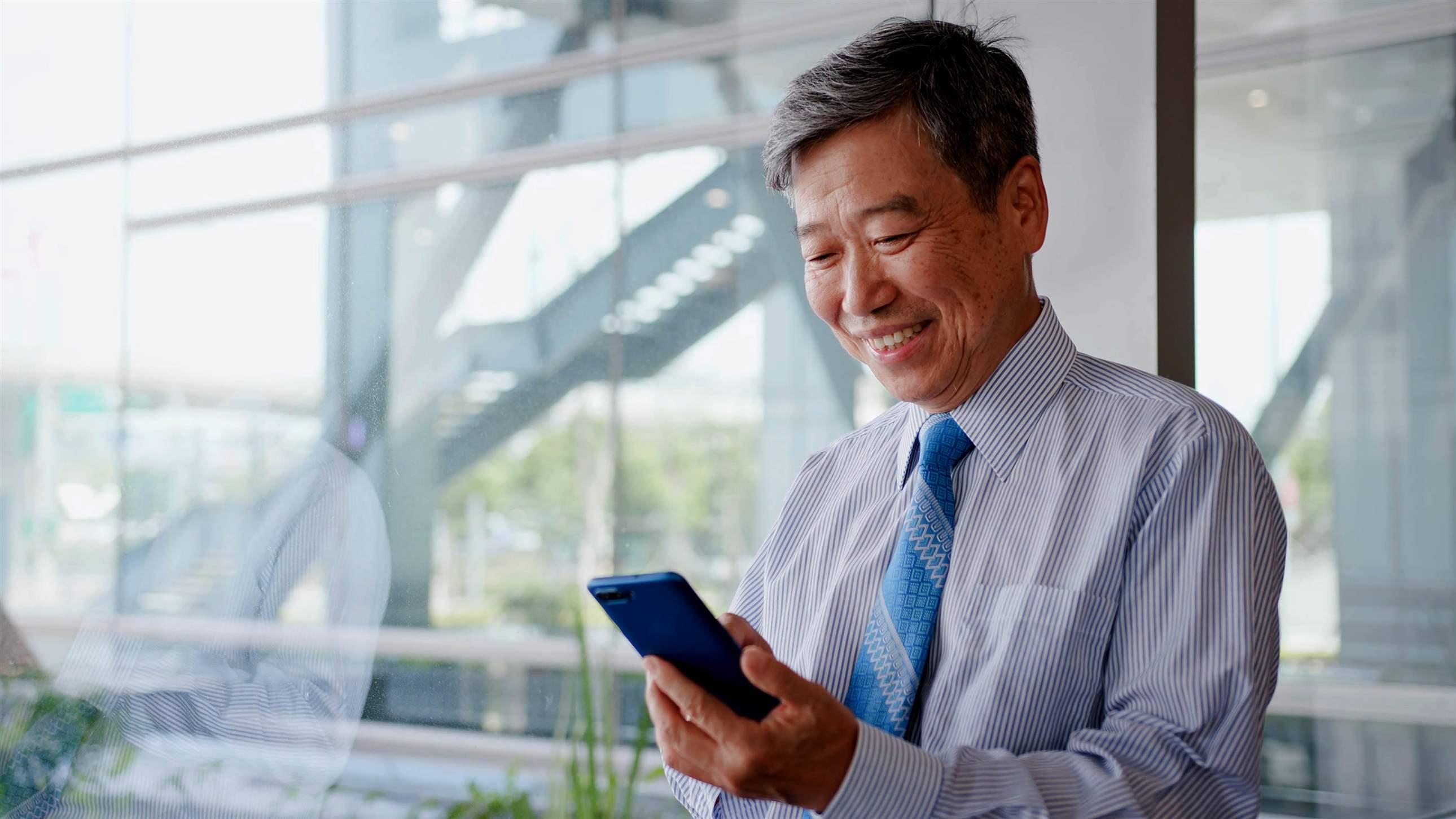 old businessman smile happily and use phone