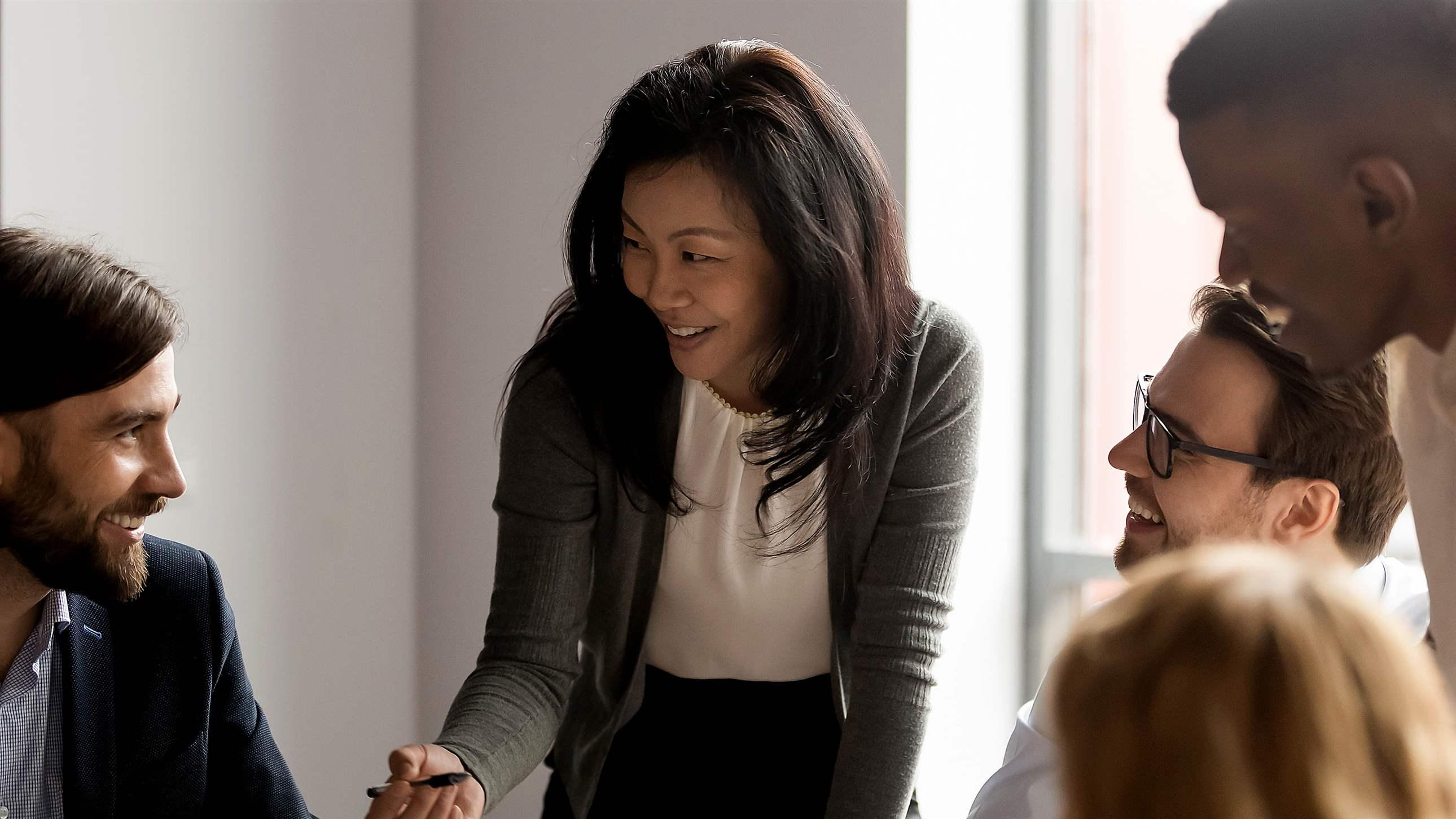 Middle aged Asian businesswoman talking to diverse colleagues at meeting, discussing project strategy and statistics, coach mentor speaking, training staff, happy business team engaged in teamwork