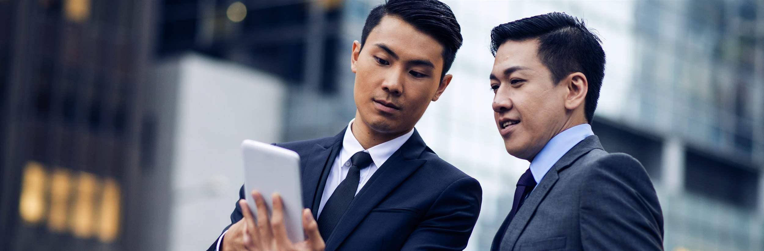 Two asian businessmen talking outdoors. One man is holding his digital tablet and looking at it. Office buildings in back, defocused.
