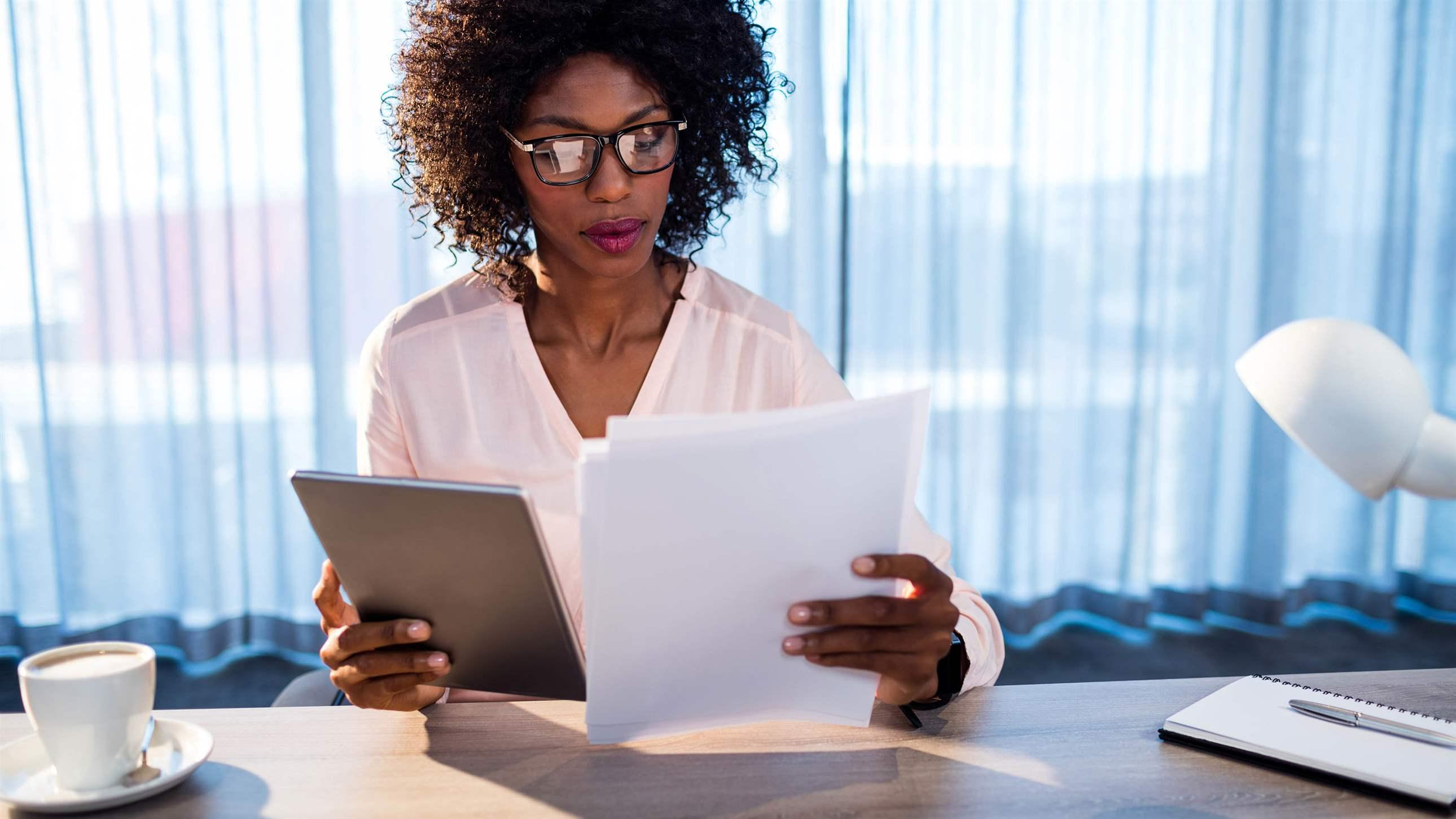 businesswoman looking at a tablet and documents