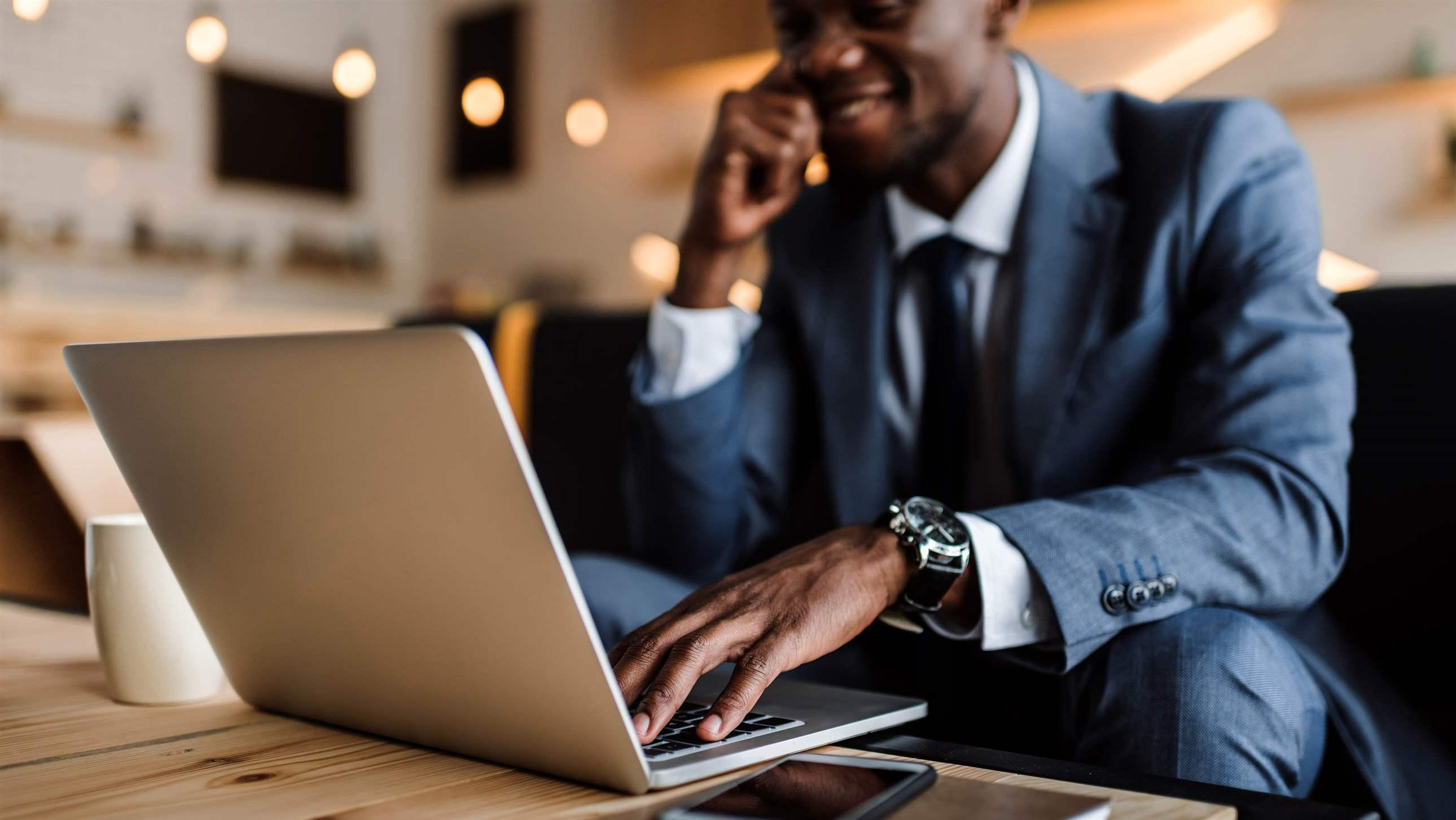selective focus of businessman using laptop in cafe