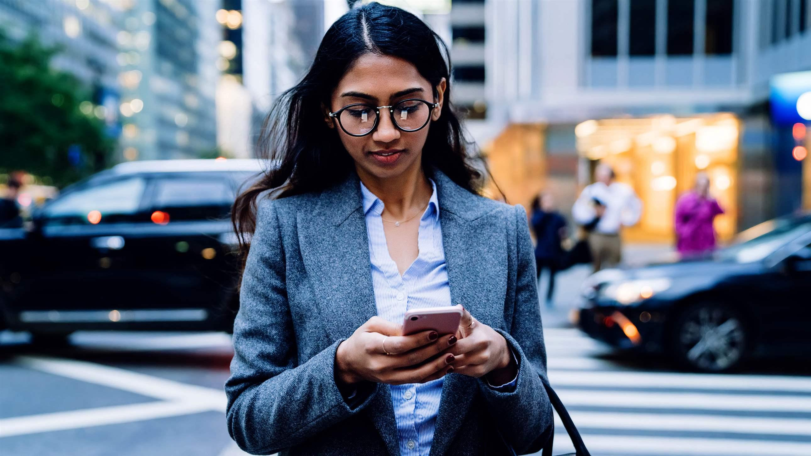 Asian business woman in glasses and gray jacket browsing in mobile phone while crossing road in New York City