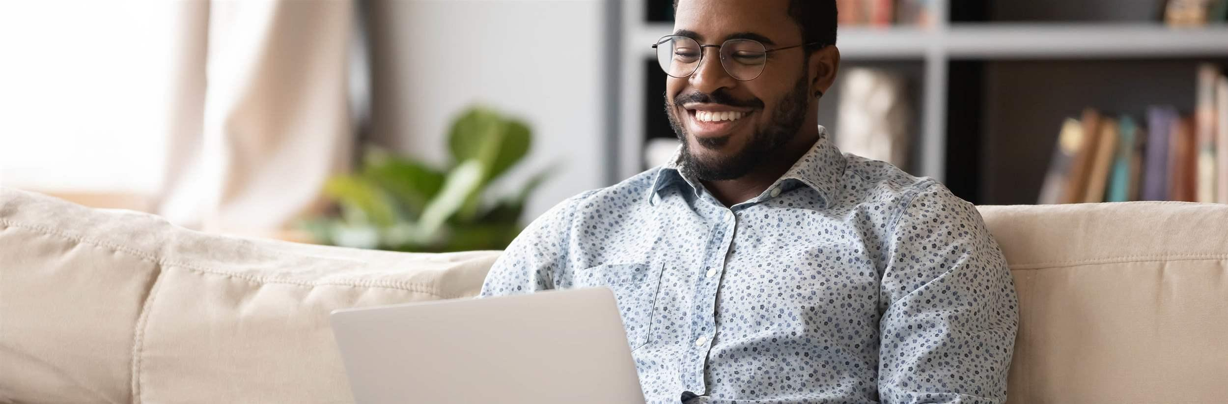 Smiling young man in eyewear relaxing on couch, looking at laptop screen.